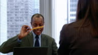 Medium shot pan man sitting at office board room table, shaking pencil in front of face and smiling/ man looking up to see coworker looking at him/ man sheepishly putting pencil down/ New York, New York