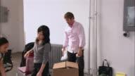 Medium shot pan man tossing tape man/ man packing box in office/ two women push box across floor/ Brooklyn, New York