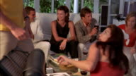 Medium shot pan men and women drinking wine + toasting in living room at dinner party