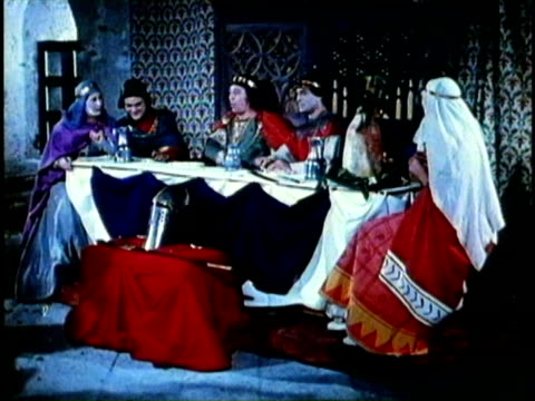 Medium shot pan men in medieval knight costumes at banquet table eating meat sloppily RECREATION medieval knights eating at banquet on January 01 1956