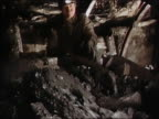 1994 medium shot pan miner ushering sulfur ore along conveyor belt / Poland