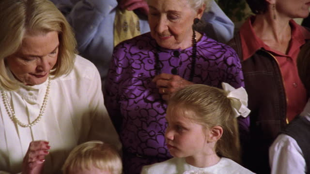 Medium shot pan multi-generational family preparing for a photo with woman smoothing small boy's hair