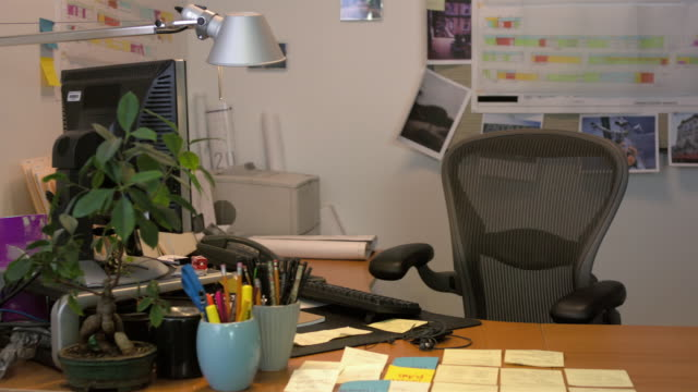 Medium shot pan of empty chair at desk in office