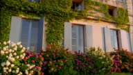 Medium shot pan of flower garden and bushes in front of chateau / France