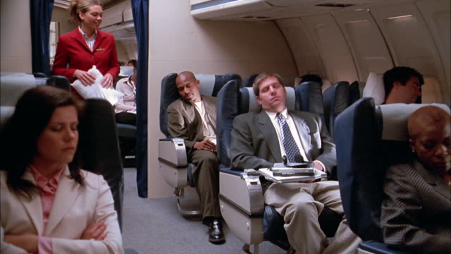 Medium shot pan passengers sleeping on airplane / flight attendant offers man pillow