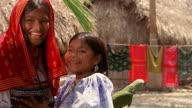 Medium shot pan past parrot and girl hugging + kissing other girl on cheek / Panama