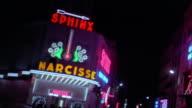Medium shot pan 'Pigalle' to 'Narcisse' to 'Eve' neon adult nightclub signs at night / Paris