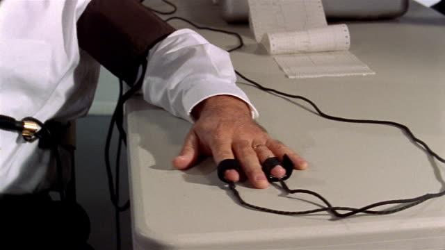 Medium shot pan polygraph machine to man taking lie detector test