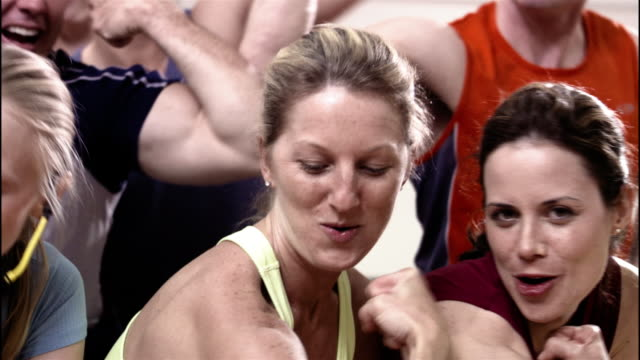 Medium shot pan portrait of men and women flexing muscles and posing in exercise class / smiling and looking at camera