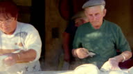 Medium shot pan senior man and woman making bread outdoors with two senior men in background / Provence, France