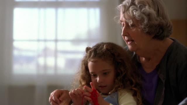 Medium shot pan senior woman and little girl with yarn
