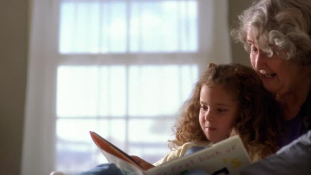 Medium shot pan senior woman reading to little girl