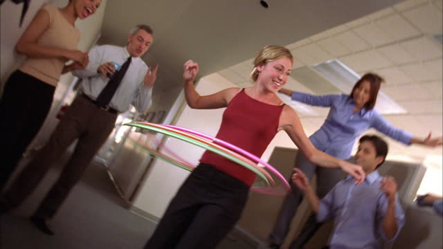 Medium shot pan shaky female office worker playing w/hula hoop, while others stand and cheer around her