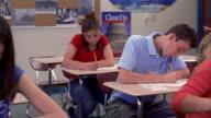 Medium shot pan students writing at desks in classroom / teenage boy looking over shoulder of girl