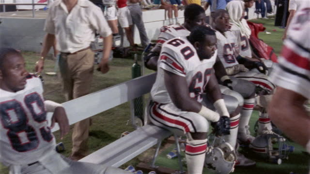 1985 Medium shot pan Tampa Bay Bandits football players resting on bench during game against Orlando Renegades / USA