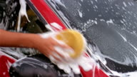 Medium shot pan teenagers washing car