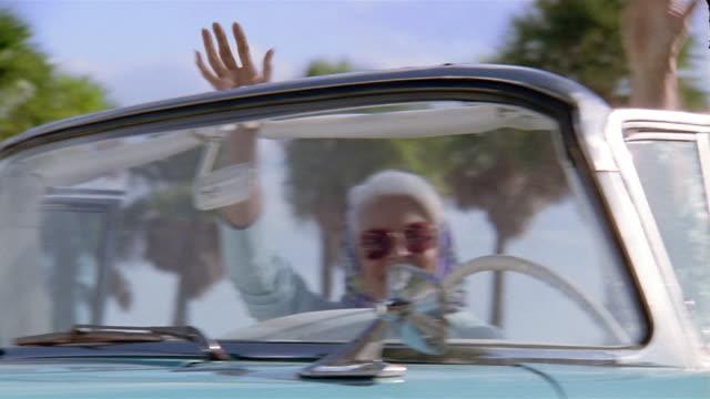 Medium shot pan three senior women waving in convertible vintage car