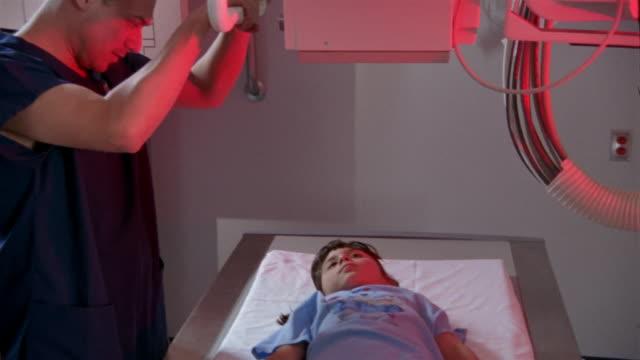 Medium shot pan tilt down nurse sliding x-ray machine away from young girl lying on table / girl sitting up