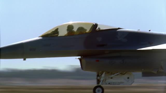 Medium shot pan to wide shot fighter jet taking off