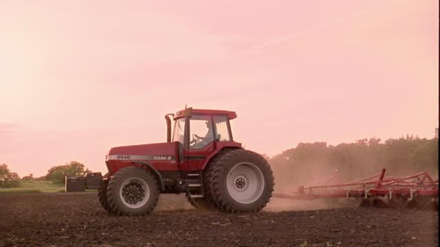 Medium shot pan tractor dragging plow across field with dust rising / Clarksville, Iowa