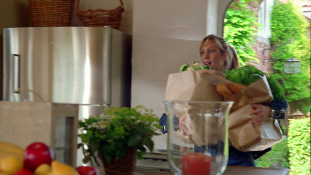 Medium shot pan woman carrying grocery bags into kitchen placing them on counter and answering telephone