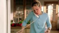 Medium shot pan woman stirring pasta in pot, adding spices and tasting pasta while talking on phone / Belgium