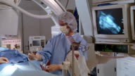 Medium shot pan woman undergoing cardiac catheterization / El Paso, Texas