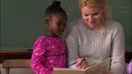 Medium shot pan young girl handing pencil to teacher / teacher writing in book