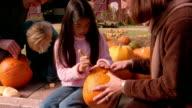 Medium shot pan zoom in mother helping daughter carve pumpkin