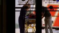 Medium shot paramedics wheeling patient on gurney from ambulance through hospital emergency doors