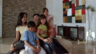 Medium shot parents and son and daughter sitting on sofa smiling at camera / young girl running and sitting on father's lap / family portrait
