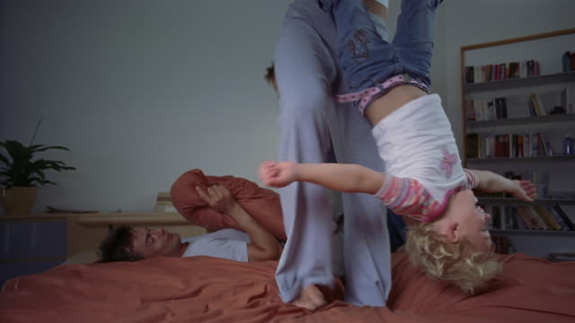 Medium shot parents playing with two children on bed / mother swinging daughter upside down / South Africa