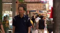 Medium shot pedestrians walking on street / Hong Kong