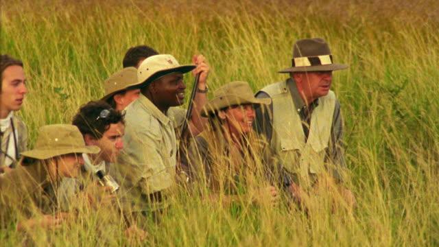 Medium shot people on safari kneeling in grass looking in binoculars and video camera / South Africa