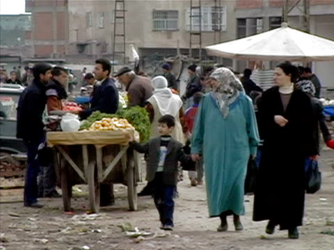Medium shot People walking and shopping in market while bulldozer drives into construction site/ Turkey