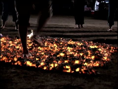 Medium shot people walking over hot coals/ California
