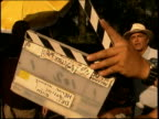 Medium shot person clapping clapboard and film director gesturing to crew next to cameraman outdoors / Mexico