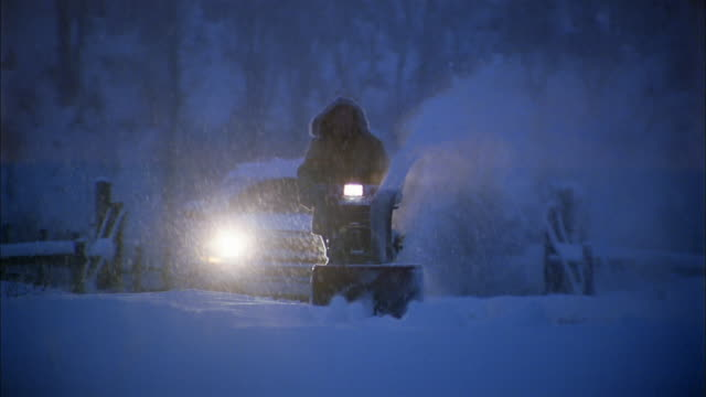 Medium shot person in hooded coat using snow blower during snowstorm at night