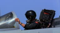 Medium shot pilot gesturing in cockpit