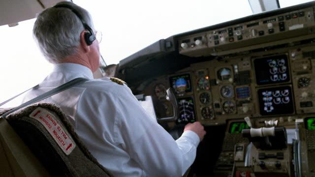 Medium shot pilot in cockpit of airplane