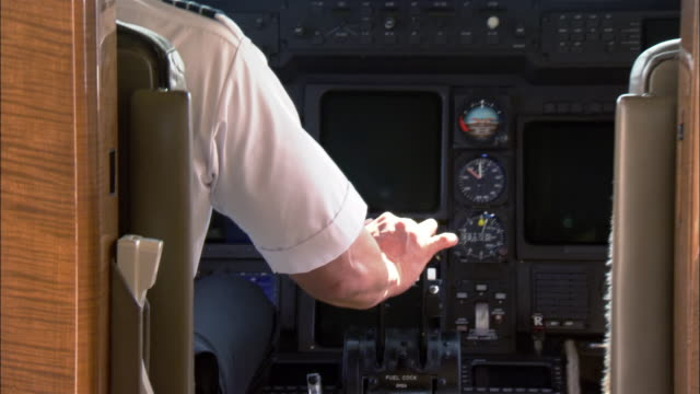 Medium shot Pilot pulling throttle in cockpit of private airplane