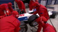 Medium shot pit crew changing tires on Formula One car during pit stop