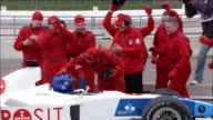 Medium shot pit crew cheering and celebrating as race car rolls into pit stop / zoom out driver hugging crew members