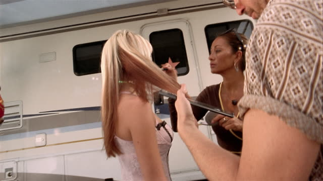 Medium shot point of view actress getting made up in front of trailer / smiling at CAM