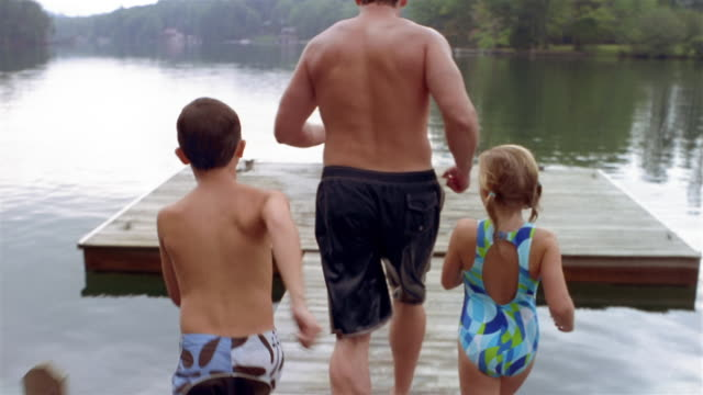 Medium shot point of view father, son and daughter running to end of dock + jumping into lake