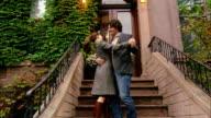 Medium shot portrait couple hugging on doorstep/ Brooklyn, New York