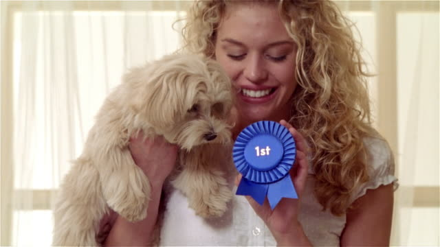 Medium shot portrait girl holding Maltese-Toy Poodle mix and first place dog show ribbon