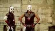 Medium shot portrait luchador duo 'Orientals' posing in front of wall/ Monterrey, Mexico