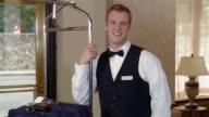 Medium shot portrait of bellhop leaning on luggage cart