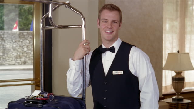 Medium shot portrait of bellhop leaning on luggage cart